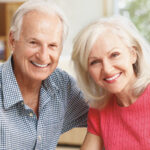 Retired couple with dental implants smiles while sitting next to each other